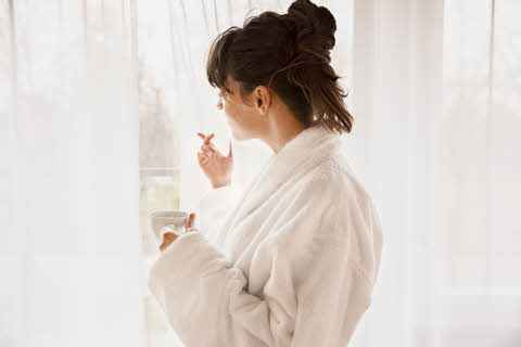 woman drinking coffee in bathrobe at scandic hotels