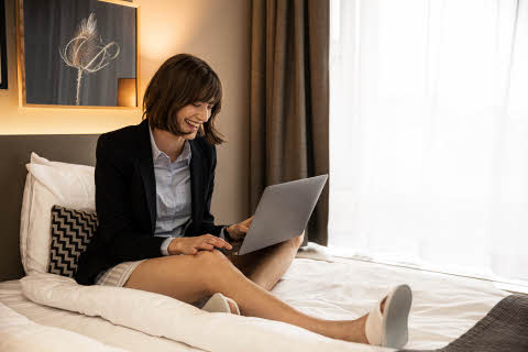 business woman in bed at scandic hotels