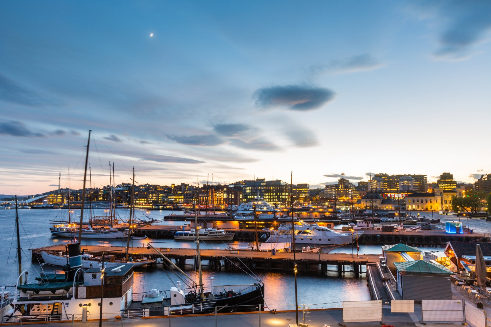 Oslo harbour with boats and yachts at twilight. There are both private and touristic boats, and on background some modern buildings.