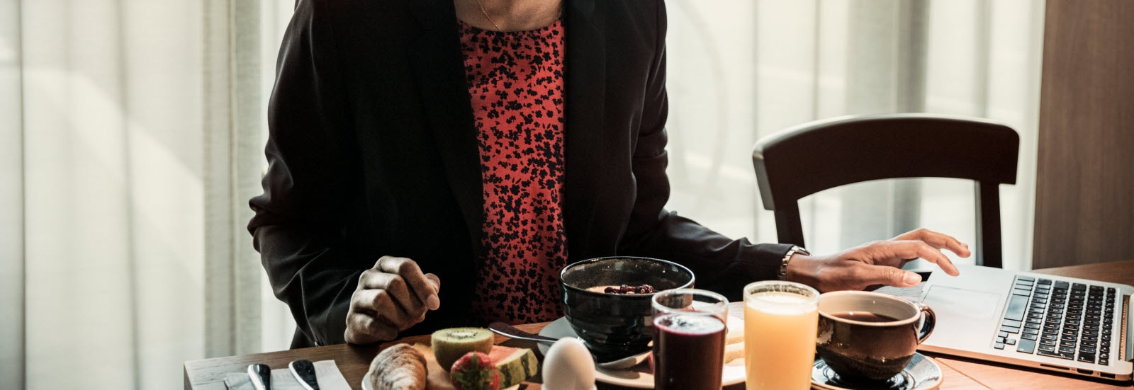Woman reading at a computer when eating breakfast