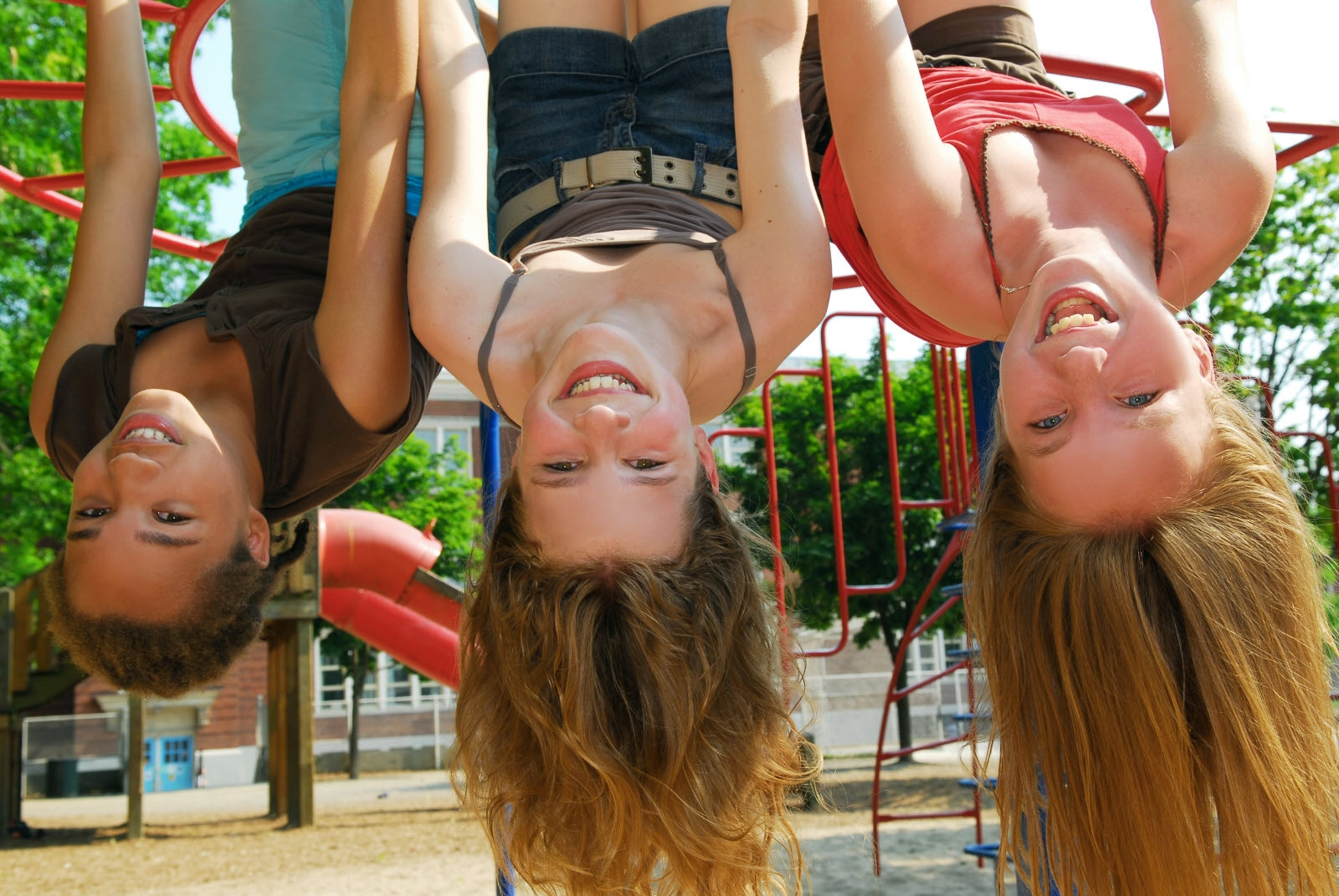 Three young girls hanging upside down in a park and laughing