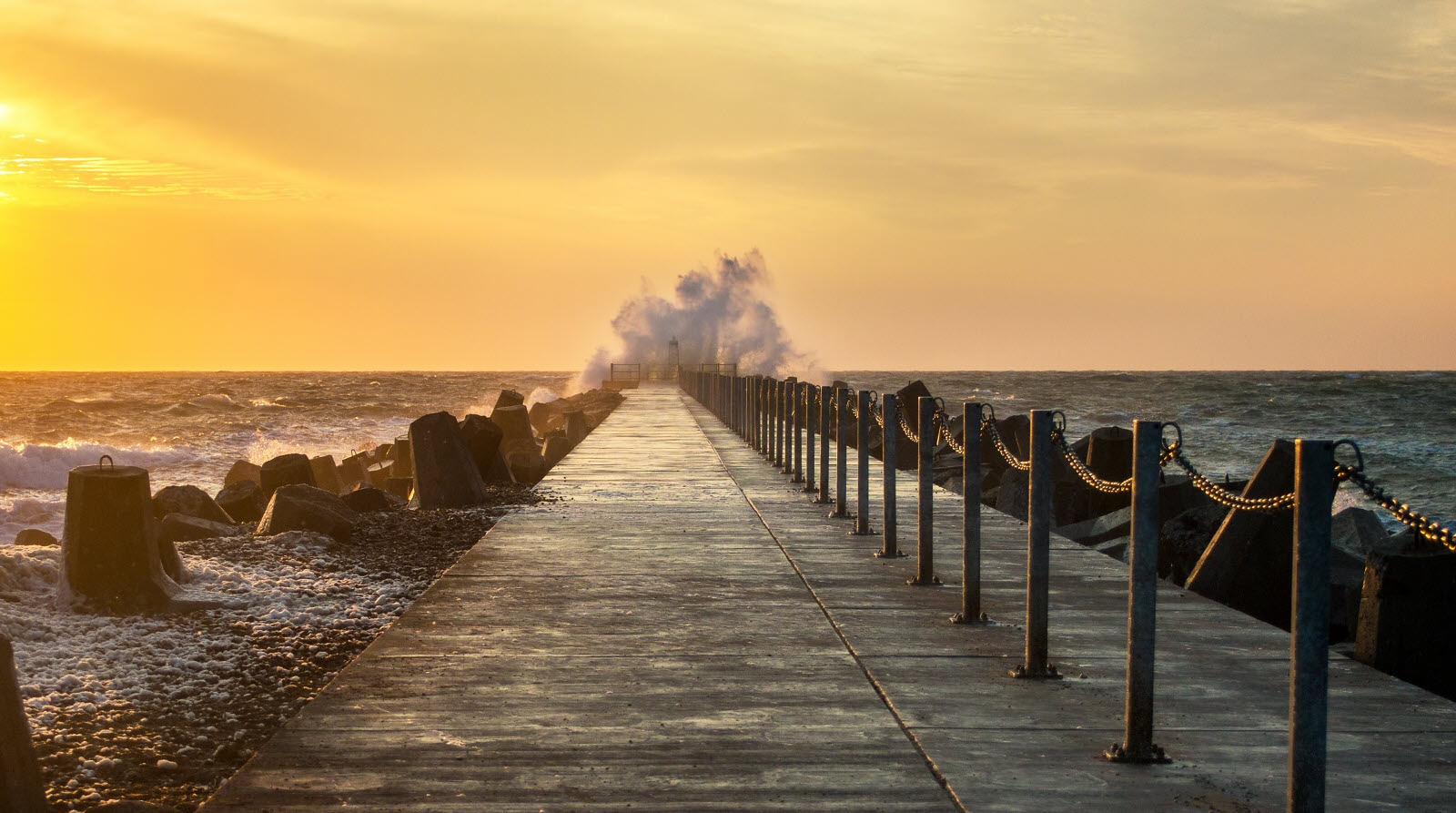 Waves over the pier, Jutland, in sunset