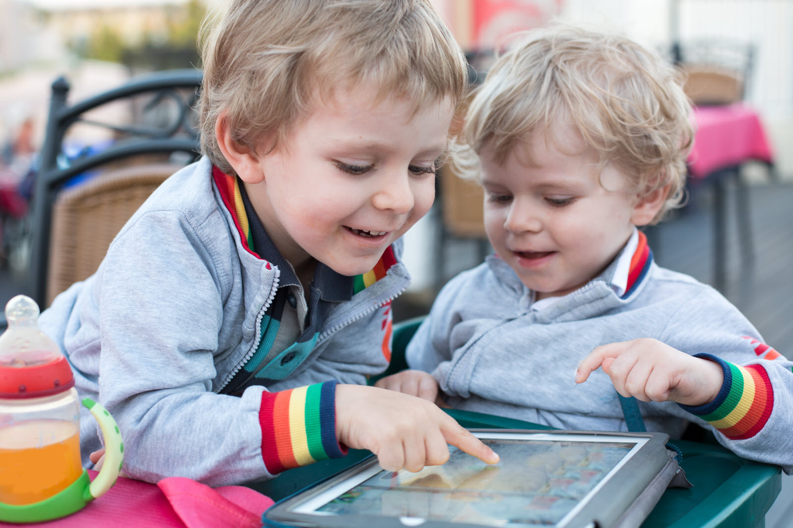 Two brother toddler boys playing with tablet