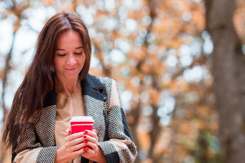 Woman drinking coffee in autumn park under fall foliage